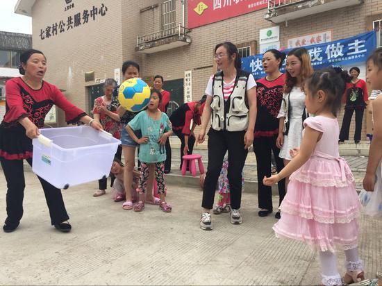 """5月29日当天,雅安市雨城区上里镇七家村的壹基金-儿童服务站举行了庆""""六一""""活动。在亲子游戏""""你投我接""""游戏中,一位奶奶正在努力接孙女投来的球。"""