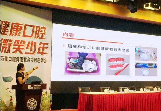 中华口腔医学会副秘书长兼科普部部长荣文笙为志愿者讲解口腔健康教育教材