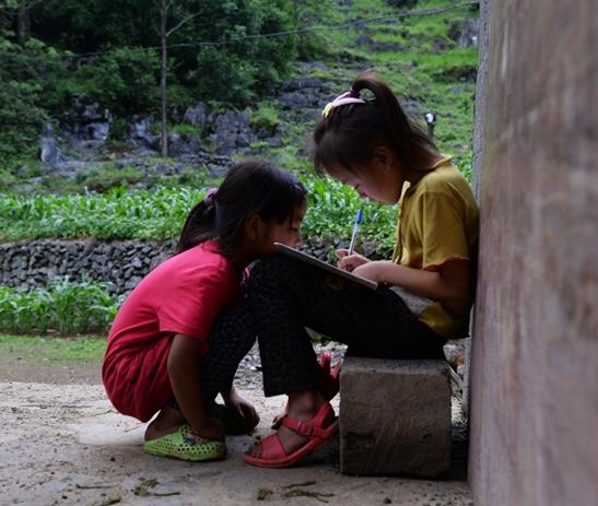 i5月28日,广西都安瑶族自治县上镇村保安乡。两个留守儿童姐妹在互相学歌,抄歌词。她们很喜欢音乐,长大后想成为歌唱家。视觉中国供图ge