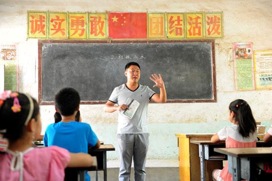 """80后青年杨承,来自甘肃省天水市,是河南第一批""""特岗教师""""中的一员。2009年,大学毕业的他,放弃了城市优裕的生活条件,来到了濮阳市黄河滩区六市小学,把梦想和希望带到农村孩子的心中。视觉中国供图(资料图片)"""