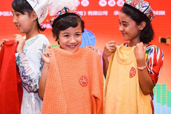受助新疆儿童拿到爱心妈妈编制的毛衣露出甜甜的笑容