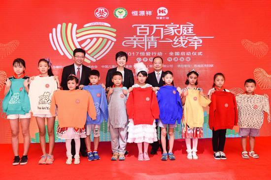 邓丽、朱锡生、陈忠伟为10名受助儿童代表赠送爱心毛衣