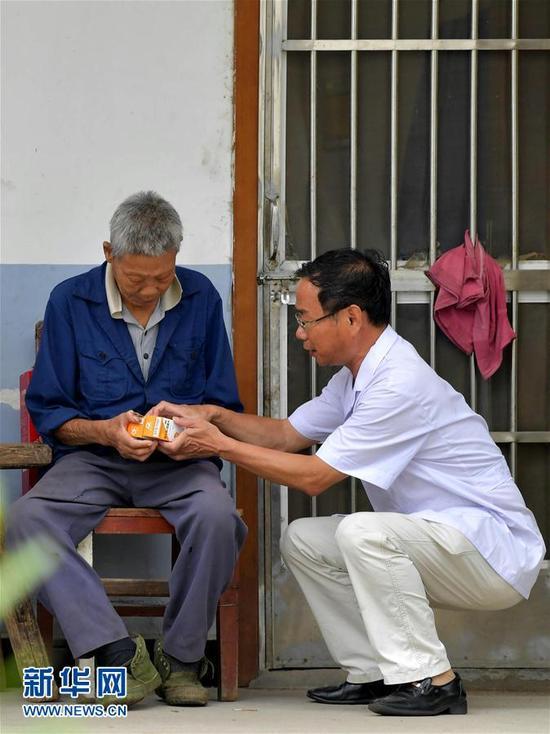 28载无怨无悔在江西省皮肤病专科医院康复中心,徐根保(右)在向一名患者介绍服用药物的具体步骤。