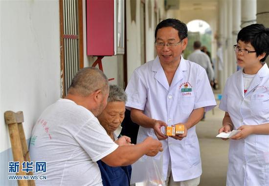 28载无怨无悔在江西省皮肤病专科医院康复中心,徐根保(右二)向患者介绍服用药物的具体步骤。
