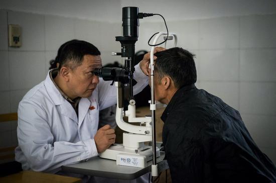 金寨县人民医院眼科郭主任为当地老人做眼部检查