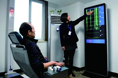 洛阳市英才社区聪明养老办事中间的任务职员在为白叟讲授仪器检测得出的各项身材情形数值(新华社记者 李安/摄)