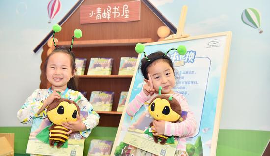 """剧场外""""环保绘本兑换""""区,两位小朋友正开心地抱着刚兑换的新绘本及""""小青蜂""""玩偶"""