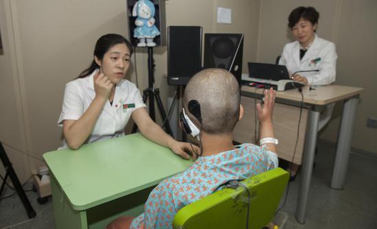 做完人工耳蜗植入手术的患儿与医生在沟通   魏星 摄