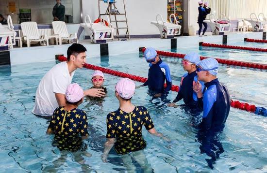 """图为著名游泳运动员、""""青春公益大使""""宁泽涛为先心病康复患儿上游泳课。"""