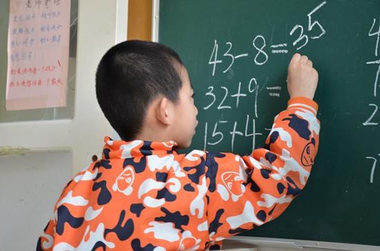 """天津""""向日葵""""自闭症康复中心,一个孩子在黑板上演算。"""