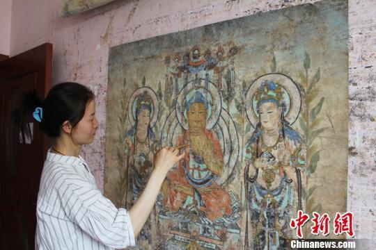 资料图。敦煌画师李玉在家中临摹莫高窟壁画。 徐雪 摄