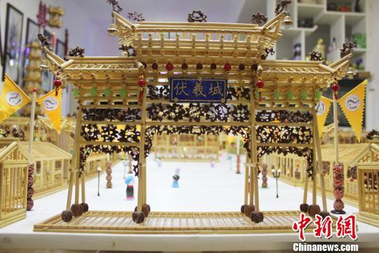 """耗时三年多时间,吴天祥用一万多根筷子和竹条,四百多颗核桃终于在近日完成了微型伏羲城的制作,精细的外观让人想不到,这竟是出自于一位""""外行人""""之手。 徐雪 摄"""