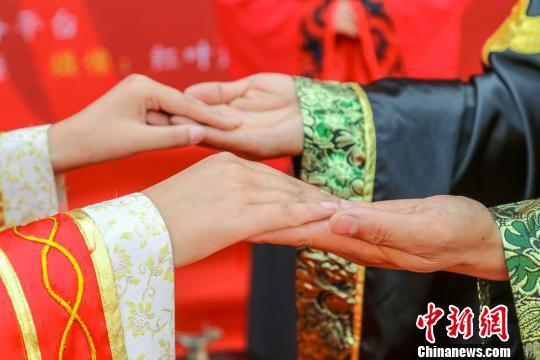 """4月19日,甘肃庆阳市举办""""小崆峒旅游文化节"""",随着舞台上公益婚俗礼仪文化展演开始,一场原汁原味的中式婚礼吸引了过往的游客驻足观看。 陈飞 摄"""