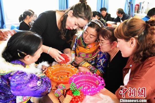 连日来,甘肃张掖市肃南裕固族自治县开展核心区搬迁农牧民手工艺品制作生产技能培训班,裕固族妇女学习制作手工艺品。 武雪峰 摄