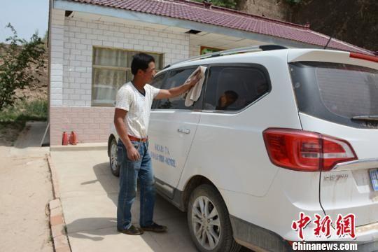 图为杨坪沟村村民张玉国擦洗汽车。 李文 摄