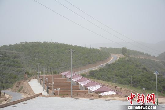 5月下旬,甘肃庆阳市环县合道镇杨坪沟村新修的柏油路旁边建起了新农村。 李文 摄