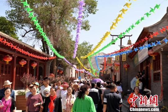 6月9日,兰州市西固区第三届文化旅游节暨河口古镇招商推介会在河口古镇举行。图为河口镇街道上游人如织。 郭炯 摄