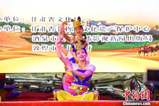 """6月9日,在""""丝路记忆""""——2018年""""文化和自然遗产日""""甘肃省非物质文化遗产宣传展示活动中,敦煌市文化馆表演的敦煌舞《壁画印象》。 王斌银 摄"""