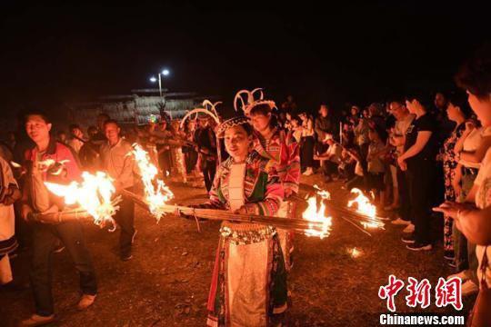 图为白马人穿戴民族服饰相约来到村广场准备将手中未燃尽的火把聚集起来点起篝火。 杨艳敏 摄