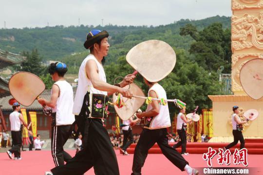 羊皮鼓是旋鼓舞的主要道具,鼓面为精制的羊皮,以铁圈为箍,外形如一面大葵扇。图为武山展演者边敲旋鼓边唱祈福歌。 张婧 摄