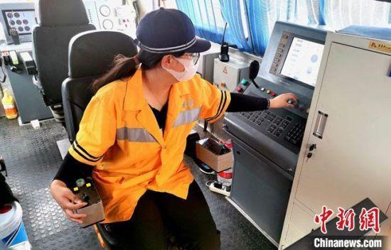 周倩是大型养路机械设备的司机,负责操控设备对铁路线路进行捣固。 俱娜 摄