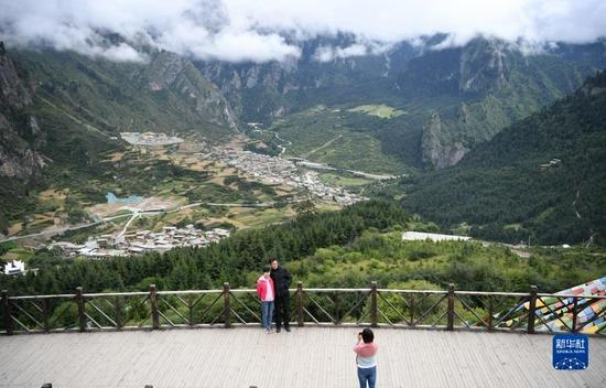 游客在扎尕那景区内的观景台拍照留念(8月28日摄)。新华社记者 杜哲宇 摄
