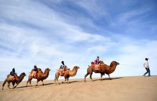 游客在敦煌鸣沙山骑骆驼(2017年5月3日摄)。新华社记者 陈斌 摄