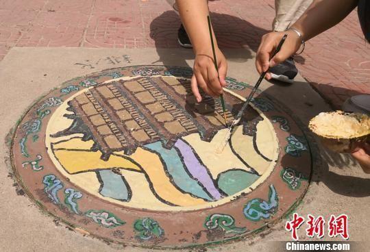 图为在井盖绘画。 刘玉桃 摄