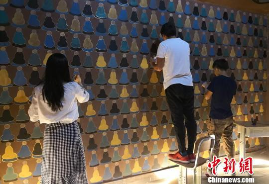图为同学在墙壁绘制千佛形象。 刘玉桃 摄