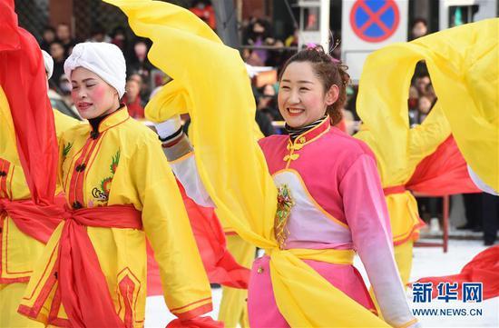 2月18日,社火队员在兰州市皋兰县县城街道进行表演。 新华社记者 范培珅 摄