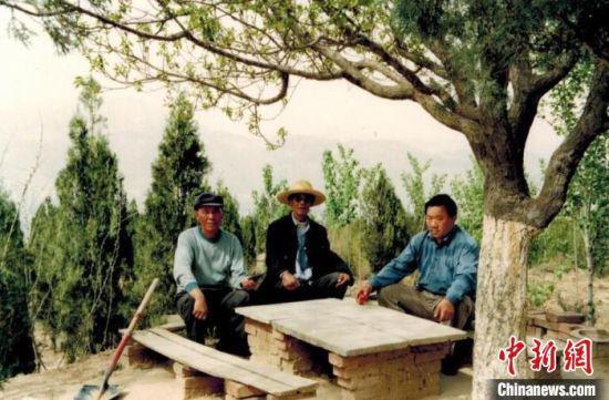 图为年轻时的汤学进(右一)与同伴在植树间隙休息,彼时山上的生态环境已有明显改善。(资料图) 受访人供图