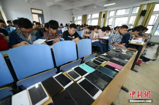 """中南大学软件学院的教室里,第一排座位上摆满了手机。为了治上课""""低头族"""",中南大学软件学院倡议学生先交手机再上课,此举得到众多师生的认可。 本文图均为 中新网 资料图"""