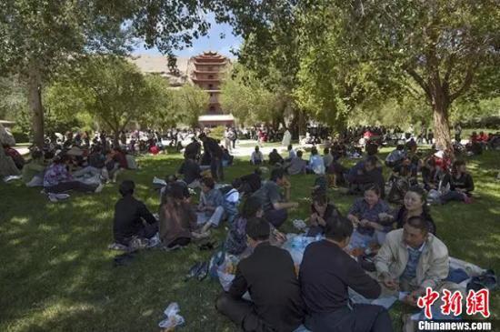 图为2007年四月初八,在莫高窟聚会的人们。在九层楼前,民众烧香礼佛,祈求幸福,直至中午,人群仍未散去。 敦煌研究院 供图
