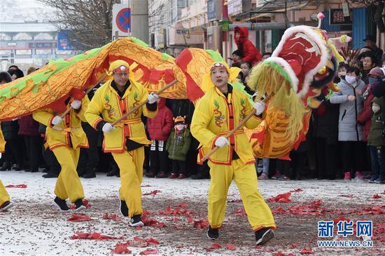 2月18日,社火队员在兰州市皋兰县县城街道表演舞龙。 新华社记者 范培珅 摄