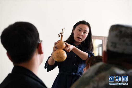 在兰州职业技术学院非物质文化遗产学院,兰州阮氏雕刻葫芦艺术第四代传人阮熙越给学生讲解雕刻葫芦技巧(4月1日摄)。
