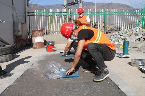 青年员工正在做路基灌砂法检测 摄影:程诚