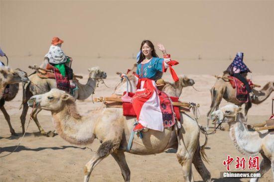 图为游客穿汉服骑骆驼畅游敦煌大漠,体验丝路风情。 王斌银 摄