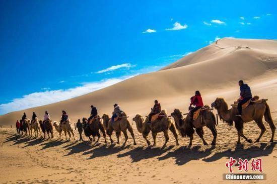 资料图:游客骑骆驼畅游敦煌鸣沙山。 王斌银 摄