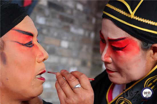 妻子张玲玲正在给丈夫王宏荣扮妆