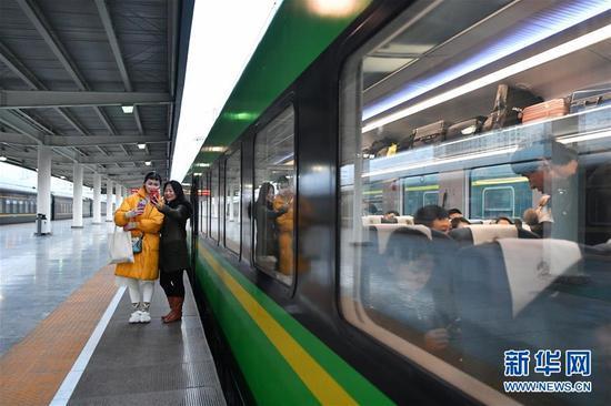 """1月8日,两位旅客在兰州至重庆北的D754次""""复兴号""""动车组列车旁拍照留念。新华社记者 陈斌 摄"""