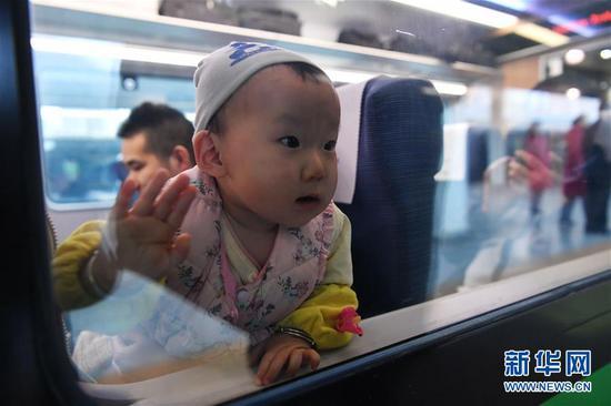 """1月8日,一位小朋友从兰州站乘坐D754次""""复兴号""""动车组列车出行。新华社记者 陈斌 摄"""