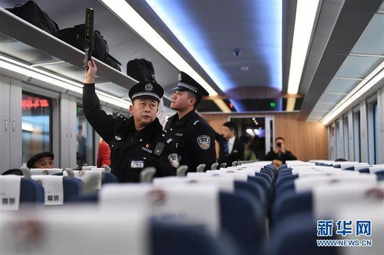 """1月8日,乘警邱永强(前)在兰州至重庆北的D754次""""复兴号""""动车组列车上查看列车行李架。 新华社记者 陈斌 摄"""
