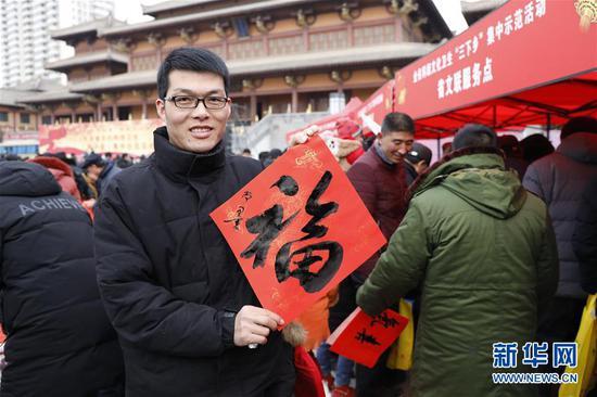 1月15日,在静宁县成纪广场,市民在展示福字。(张智敏 摄)