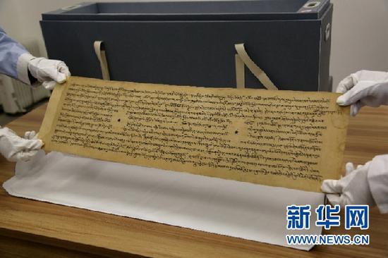 敦煌市档案馆工作人员展示修复后的唐代藏文写经。新华网发(张晓亮 摄)