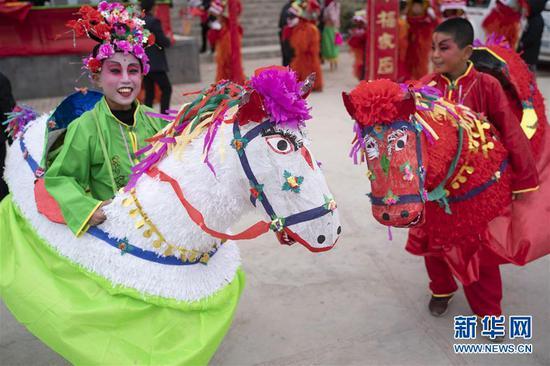 2月19日,在甘肃省陇南市武都区马街镇官堆村,社火队小演员参加巡游表演。 新华社记者 才扬 摄