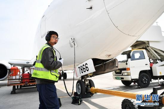 2月22日,机务人员滑翔在停机坪对一架飞机进行起飞前检查工作。新华社记者陈斌摄