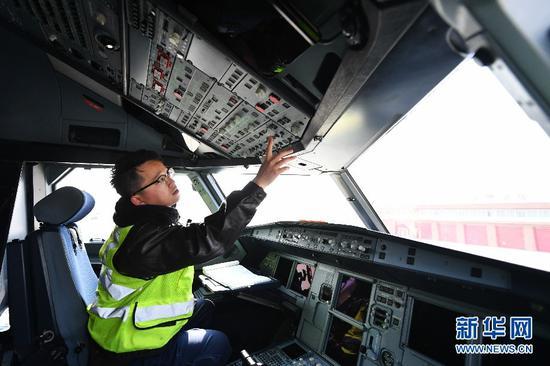 2月22日,机务人员陈赫在飞机驾驶室内检查。新华社记者陈斌摄