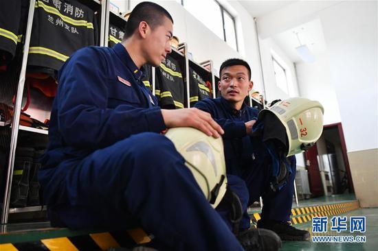 李志亮(右)与队友交流经验(4月11日摄)。 新华社记者 陈斌 摄