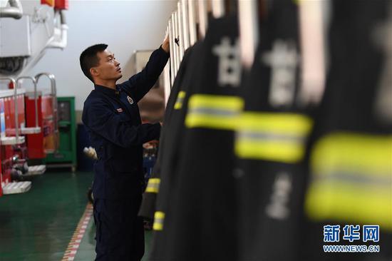 李志亮在整理消防救援服(4月11日摄)。新华社记者 陈斌 摄