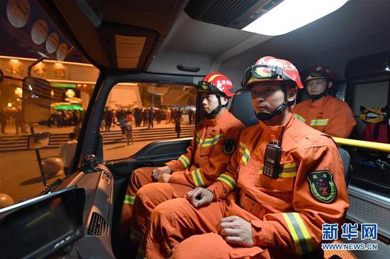 李志亮(前右一)和队友夜间在兰州市西固区金城公园门前执勤(4月11日摄)。 新华社记者 陈斌 摄